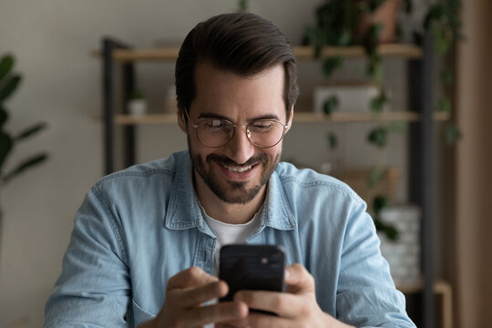 Surfing virtual world. Happy smiling bearded millennial male in glasses hold cellphone in hands use business entertainment application engaged in online chat. Modern day young man addicted to gadget