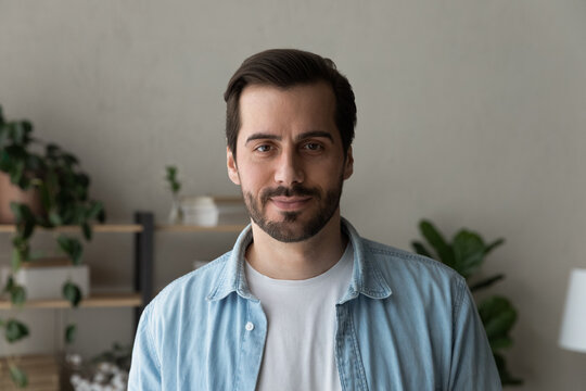 Headshot portrait of handsome bearded millennial man wearing casual clothes. Calm positive young guy standing indoors at home in office looking at camera with pleasant confident smile. Profile picture