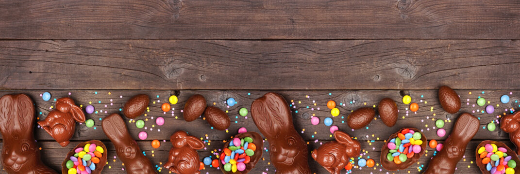 Easter candy and chocolate bunnies and eggs. Bottom border against a rustic dark wood banner background. Copy space.