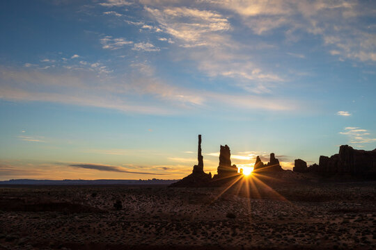 A starburst effect pierces through rock formations at Monument Valley
