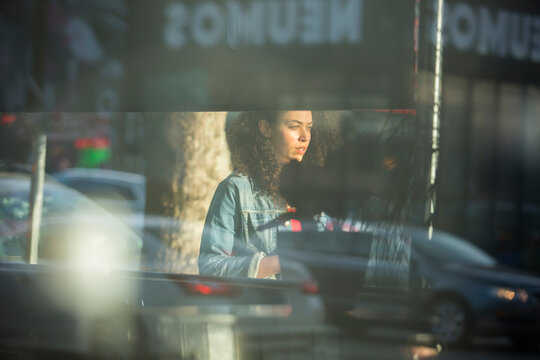 Street portrait of woman with layered reflections of the city
