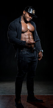 Strong athlete in dark jeans poses to the camera on black background. Unbuttoned black shirt and perfect abs. Portrait of an afro american bodybuilder with phone in hands.