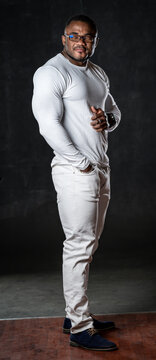 Full length portrait of african american in white long sleeve shirt and white jeans. Contrast background. Muscular sportsman. Closeup.