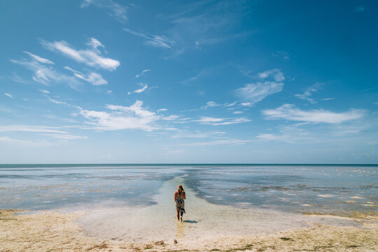 Young woman looking at her path out into the ocean
