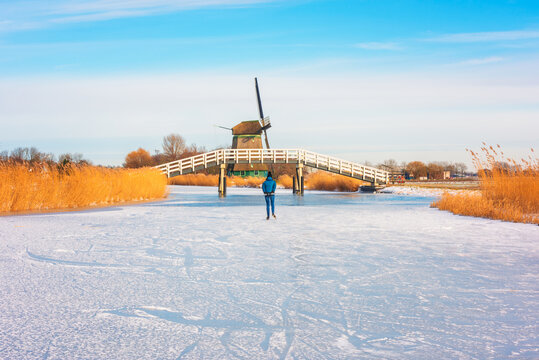 Lone Ice Skater skating on a frozen polder ditch in Obdam, Netherlands on a cold February day in 2021