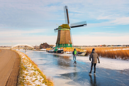 Two Ice Skaters skating on a frozen polder ditch in Opmeer, Netherlands on a cold February day in 2021