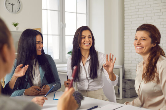 Smiling charismatic female team leader talking to employees in corporate meeting. Group of happy young business women sitting at office table, discussing ideas, sharing funny stories and laughing