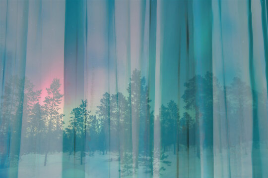 View of snowy woods and colourful dusk sky looking through window with sheer curtains nobody