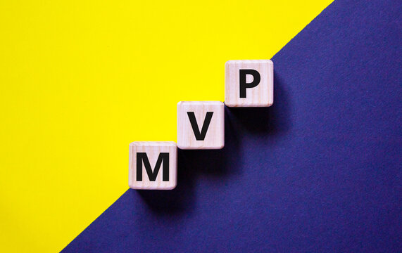 MVP, minimum viable product symbol. Wooden cubes with the word MVP, minimum viable product. Beautiful yellow and black background. Business and MVP, minimum viable product concept, copy space.