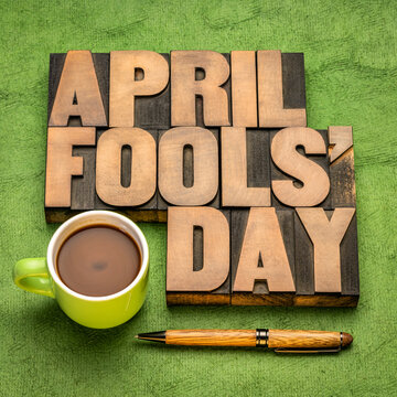 April Fools' Day word abstract in vintage letterpress wood type with a cup of coffee, prank and practical joke concept