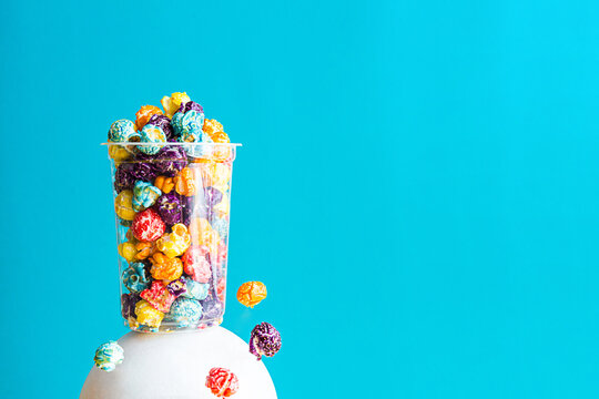 Creative composition with colored popcorn in a transparent glass on a blue background. Modern abstract still life with copy space