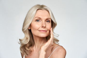 Fototapeta Beautiful gorgeous 50s mid aged mature woman looking at camera isolated on white. Mature old lady close up portrait. Healthy face skin care beauty, middle age skincare cosmetics, cosmetology concept