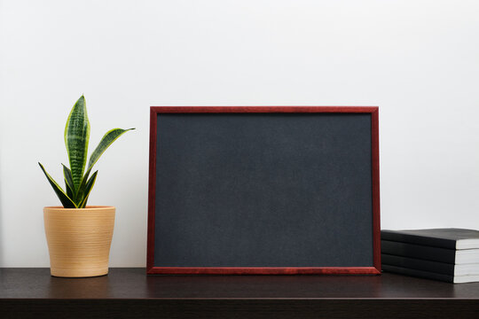 Brown wooden frame or chalkboard mockup in landscape orientation with with a cactus in a pot and book on dark workspace table and white background