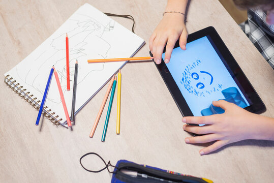 High angle view of boy drawing on tablet computer at table