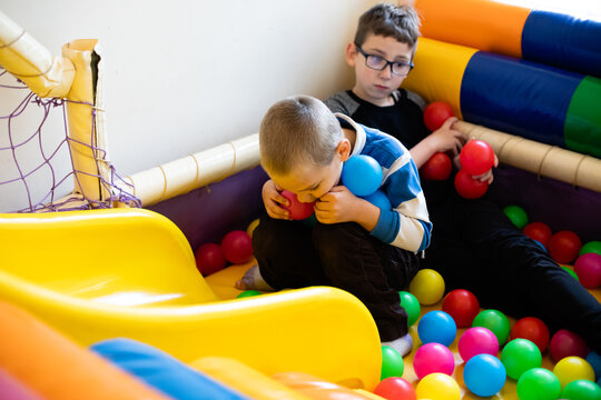 Boys play in pool with soft plastic balls