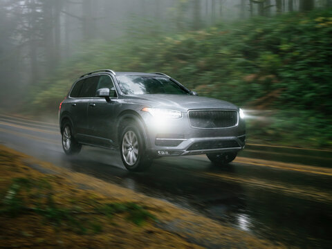 SUV automobile driving through foggy and rainy forest road