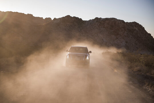 Off-road car driving dirt road in front of mountains with dust backlit
