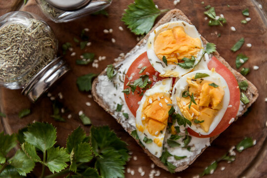 Top view of sliced bread with eggs, tomatoes and sour cream. Diet sandwich from above.