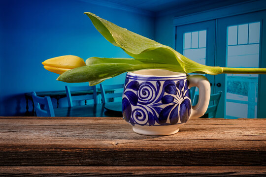 Still life of a closed yellow tulip placed on a blue and white Mexican pottery mug on a barn wood table in front of a bluish dining room