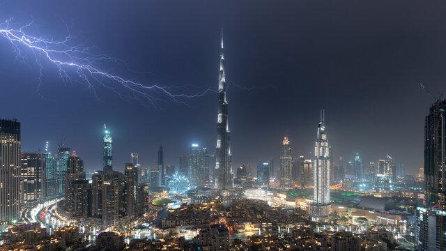 Dubai skyline and Burj Khalifa under stormy night sky with lightning