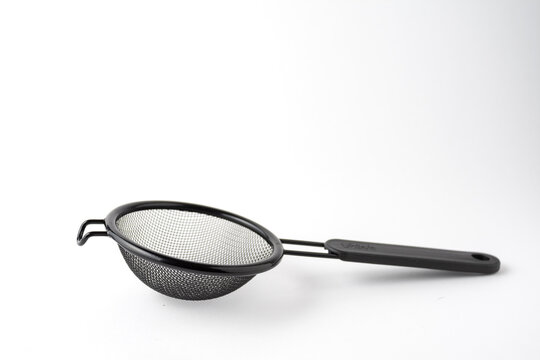 Top view of black metal strainer, on white background, horizontal, with copy space
