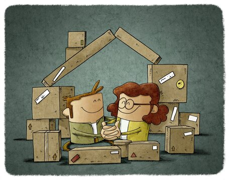 A couple in love are among some cardboard boxes that form the shape of a house. home buying concept