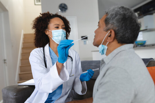 Senior mixed race man with female doctor home visiting wearing face masks taking swab test