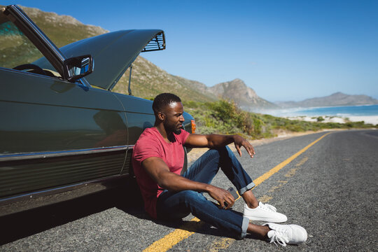 African american man holding smartphone sitting on road beside broken-down car with open bonnet