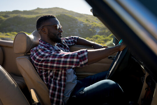 African american man driving on sunny day in convertible car holding driving wheel