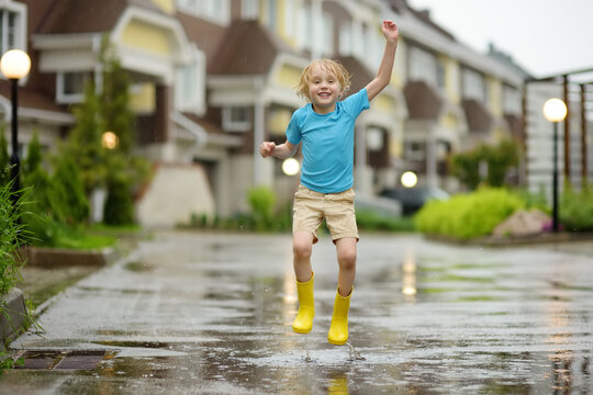 Little boy wearing yellow rubber boots jumping in puddle of water on rainy summer day in small town. Child having fun.