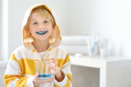 Little boy is learning carefully brush teeth. Child using liquid for disclosing plaque. Teaching children proper oral hygiene. Dental medicine for kids.