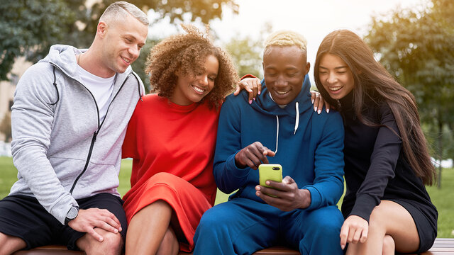 Young black guy sharing his mobile phone, showing funny joke in social media to his multiethnic friends, sitting together on bench in park