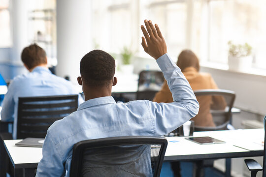 Back view of black guy student raising hand