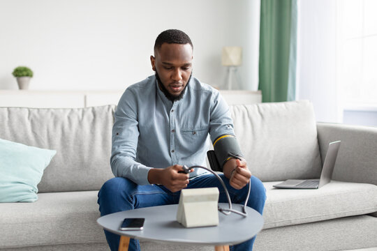 African Man Measuring Arterial Blood Pressure Sitting At Home