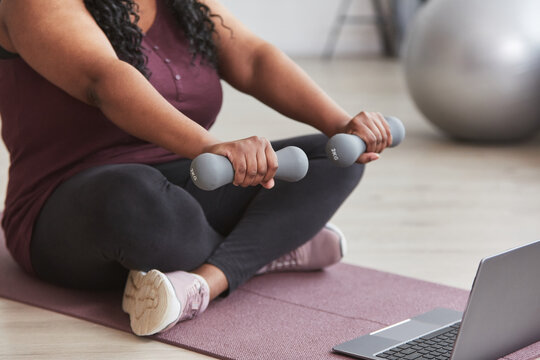 Cropped shot of curvy African American woman working out at home with dumbbells while sitting on yoga mat and watching online training videos, copy space