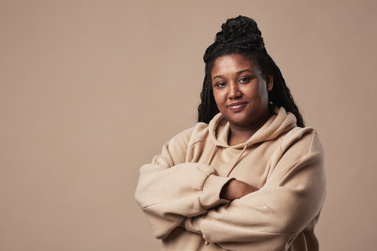 Minimal waist up portrait of confident curvy woman looking at camera and wearing comfortable hoodie while standing with arms crossed against neutral beige background in studio, copy space