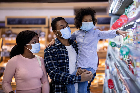 Millennial black family wearing protective masks while shopping for milk products at dairy section of modern supermarket
