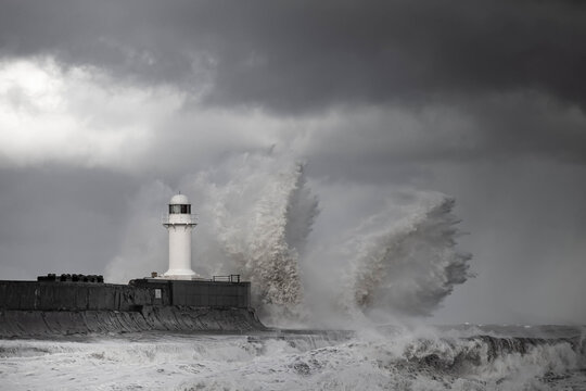 Wintry and stormy seas crashing over breakwater with lighthouse