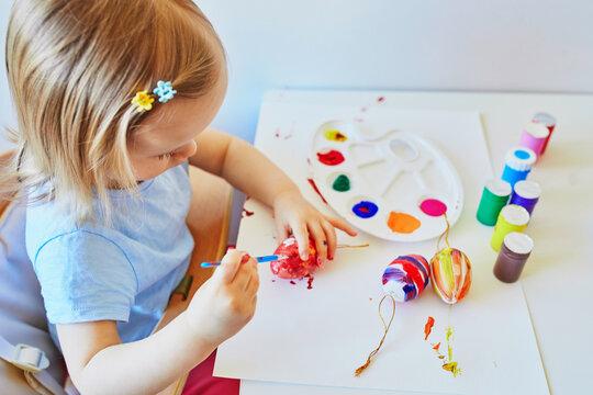 Adorable little girl painting eggs for Easter