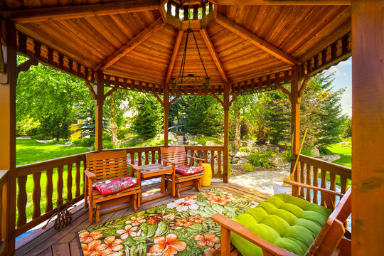 View of a wooden gazebo in the landscaped garden of an upscale home.