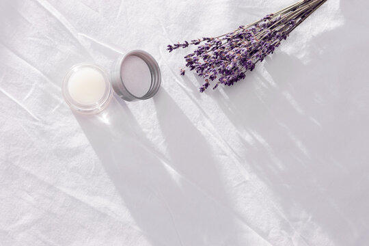 Balsam with  lavender essential oil and dry flowers on white bedclothes. Scent of lavender improves sleep and alleviates insomnia.