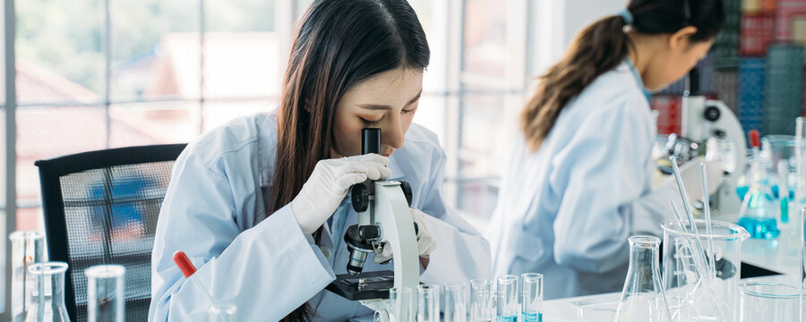 Young Asian female scientist doing research in laboratory wearing lab coat and gloves with colleague in background to develop antivirus vaccine