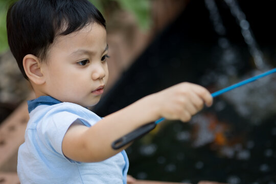 Portrait of Asia boy playing at koi pond