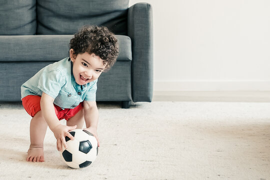 Happy little boy playing with soccer ball at home, smiling and looking at camera. Cute infant standing on carpet barefoot and having fun in living room. Holiday, weekend and childhood concept