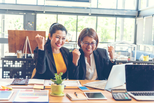 Happy success business woman partner working together in company office corporate executive teamwork. Meeting Executive Asian business woman using laptop office desk with fist arm raised win happiness
