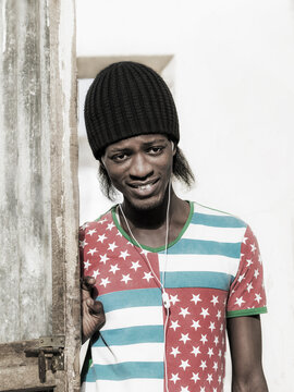 Young African listening to music and smiling in the street, cool attitude, photo