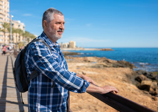 An elderly man stands in Torrevieja and looks out over the Mediterranean. He is wearing a small backpack and has his hands on the wooden railing. In the background is the promenade and the stone bank.