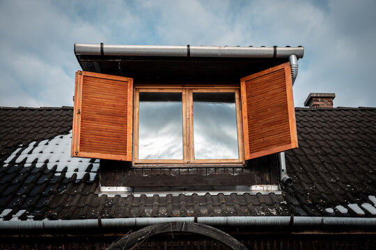 Old dormer window with sky reflection