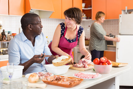 Two European women and African American man cooking together at kitchen