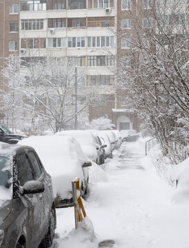 Cars in the yard of house during heavy snowfall in Russia